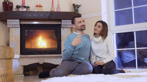 Happy couple drinks champagne relaxing near fireplace Footage