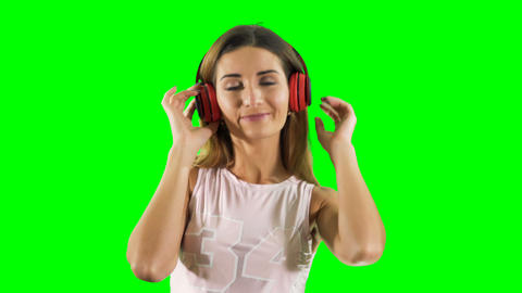 Joyful girl in headphones listen music and dances at green background Footage