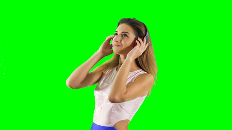 Beautiful girl listens music in headphones at chroma key background Footage