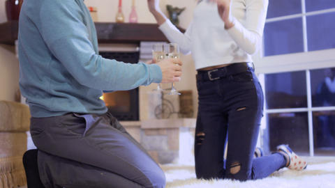 Husband brings champagne to his wife laying on floor near fireplace Footage