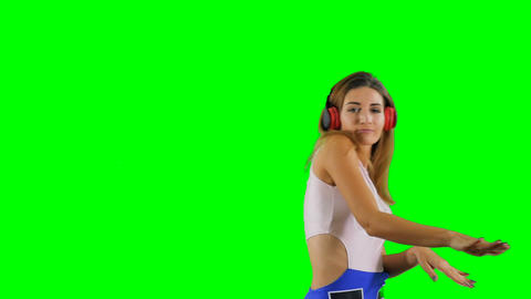 Energetic girl in headphones is listening music against chroma key background Footage