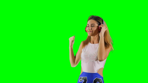 Happy young girl listens music with earphones at green background Footage