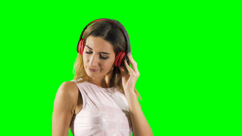 Beautiful blonde in earphones enjoys of listening music at green background Footage