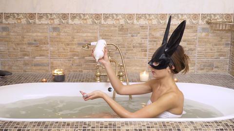 Bunny girl pours a shower gel inside her hot bath Footage