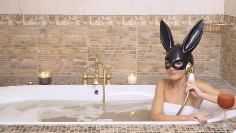 Sexy bunny drinks tomato juice and pretend to talk on phone taking a hot bath Footage