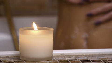 Burning candle in bathroom, woman washes her body at background Footage