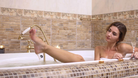Beautiful girl with champagne relax in hot bath Footage