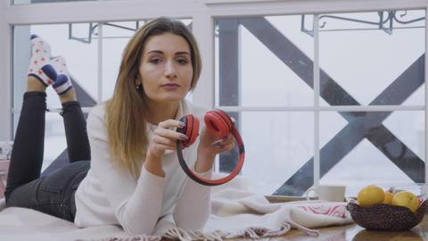 Beautiful girl listens music in headphones laying on plaid near the window Footage