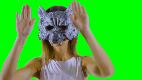 Happy girl wearing wolf mask dances at green background and shows thumbs up Footage