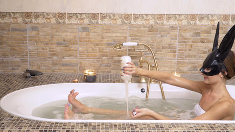 Girl in bunny mask relaxes in hot bath Footage