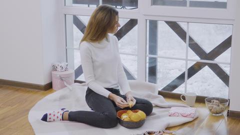 Young girl eats mandarin enjoying a winter view Footage