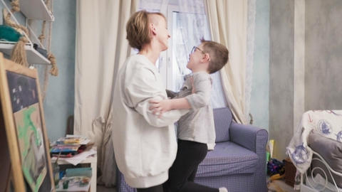 Little boy runs to his mother, they hug and whirl Live Action