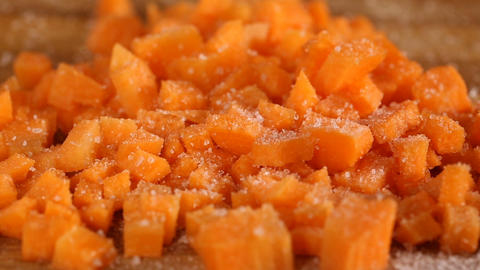 Sprinkling salt over little squares carrots on chopping board Footage