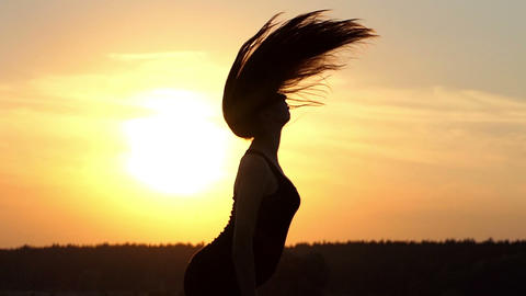 Beautiful sunset with young girl that play with her hairs Footage
