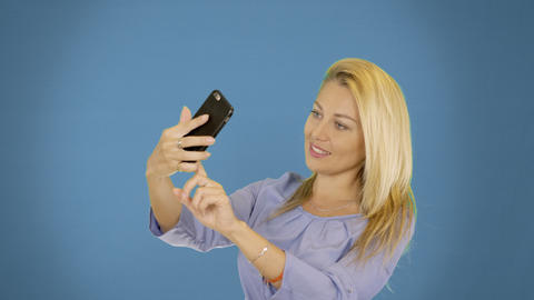 Portrait of excited cheerful smiling young pretty woman making selfie photo on Footage