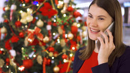 Woman near decorated Christmas tree. Pretty female using mobile receiving Footage
