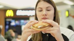 MOSCOW, RUSSIA - CIRCA November 2017: Hungry girl eating hamburger at McDonald's Footage