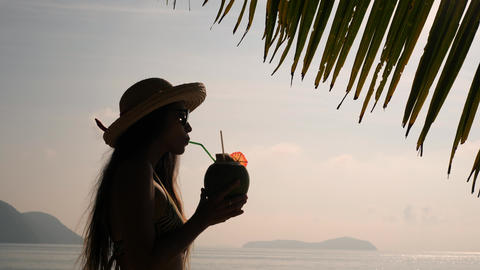 Sunset Silhouette of Young Tourist Girl Drinking Fresh Thai Coconut Water Footage