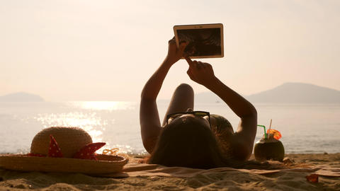 Young Tourist Girl Lying, Sunbathing on Tropical Beach and Using Mobile Tablet Footage