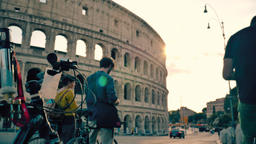 Friends riding bicycles in front of Colosseum in Rome Footage