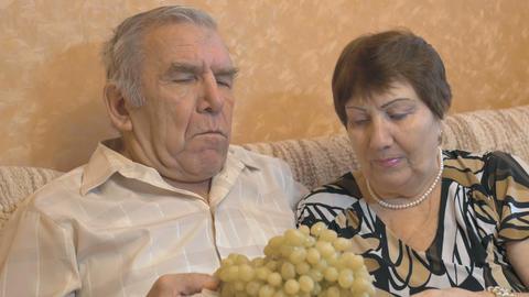 Elderly couple eating grape berries 画像