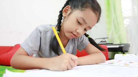 4K Asian little girl doing home work on the table 001 Footage