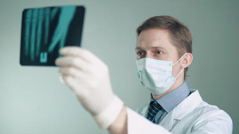the doctor is engaged in the treatment of patients. examines a patient's x-ray Footage
