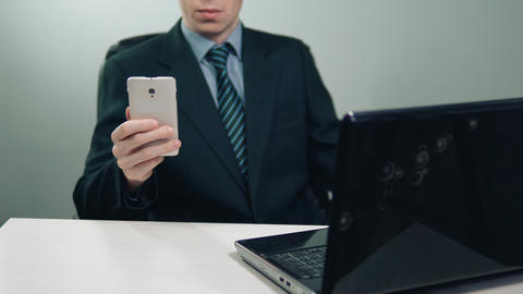 businessman in suit using phone and laptop 画像
