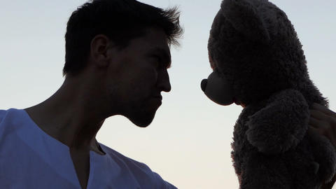Man play with big toy bear at sunset in slow motion 画像