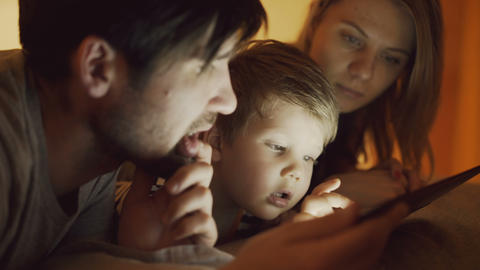 Closeup of Happy young family lying in bed at home while little boy learning to Footage