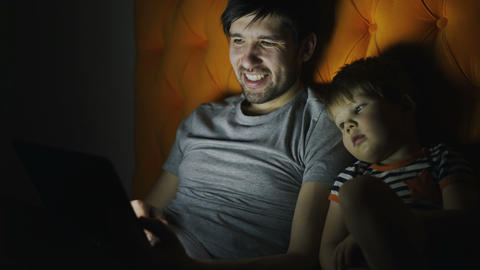 Young father and his little son watching cartoon movie using tablet computer and Footage