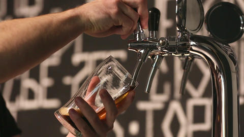 The bartender pours a dark beer in glass close-up Live Action