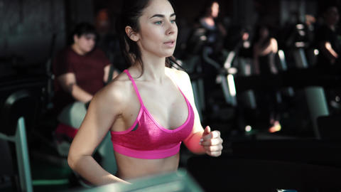 closeup portrait of a girl on the treadmill on the background of people Footage
