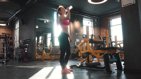 girl is drinking water while exercising in the gym. girl in sports clothes in Footage
