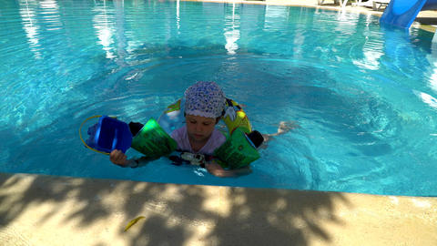 Happy little child, bathes and swims in the pool. Little girl loves to swim Footage