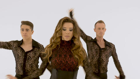 A woman and two men are dancing against a white wall. A woman falls into the Footage