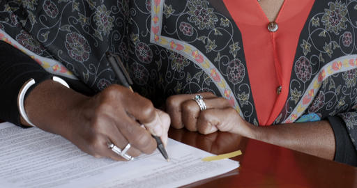 Black senior woman over 50 signing her name on legal paperwork or contracts with Footage