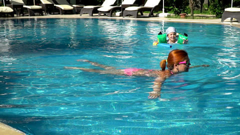 Young Mom Swimming With Her Little Daughter In A Swimming Pool 0
