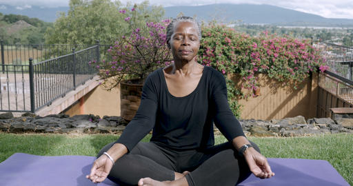 African American elderly woman in her 60s sitting quietly mediating with her Footage