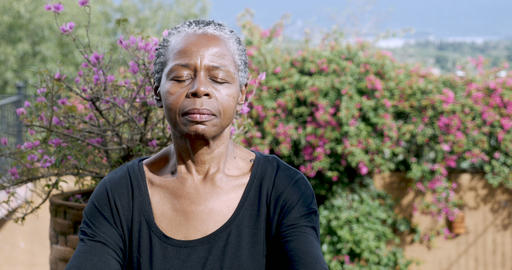 Attractive African American senior woman meditating outdoors with her eyes Footage