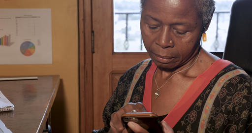 Attractive African American woman using her smart phone technology app in her Footage