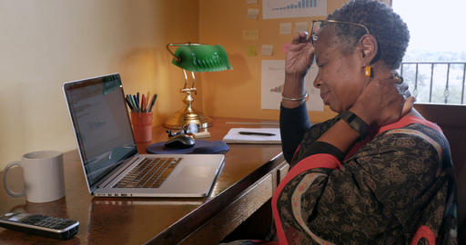 African American woman working at home office experiencing neck pain while Footage