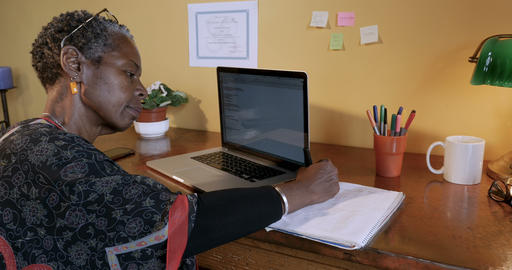 Attractive successful African American woman working at her desk writing in a Footage
