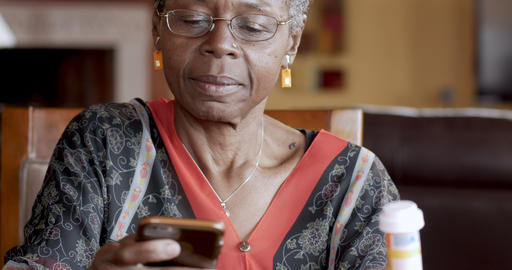 Attractive black senior woman over 50 refilling her prescription to a pharmacy Footage
