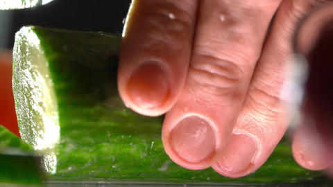 Man cutting cucumber for vegetable salad. Extreme close-up shot Footage