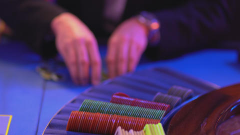 Groupier collects and sorts gaming chips on Roulette table Footage