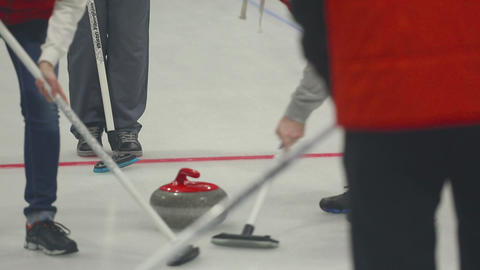 Curling stone slide, players sweeping Footage
