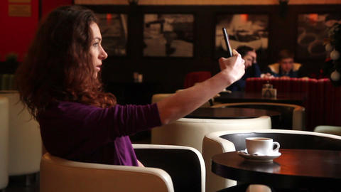 woman in a cafe at table make selfie Live Action