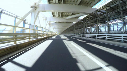 Sunshine POV view over Tokyo Rainbow Bridge's empty lower deck Footage
