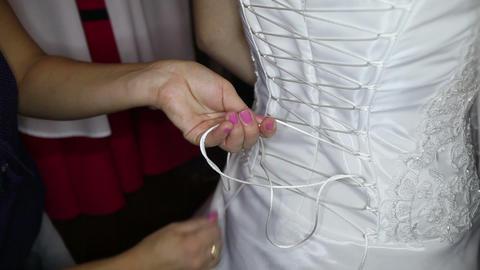 girl assistant ties corset to bride Footage